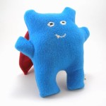 Blue super monster with red cape. Plush toy.